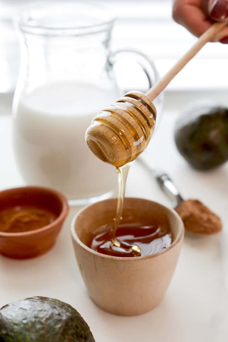 hand holding wooden honey dipper with honey drizzling back into bowl