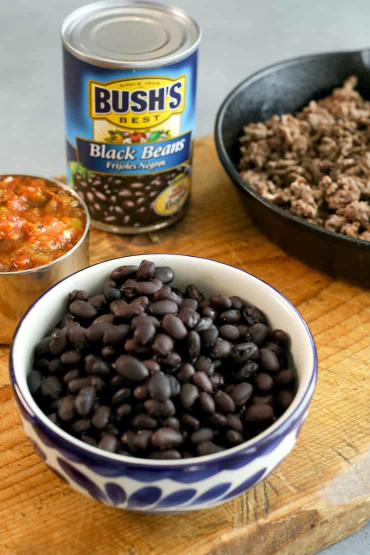 bowls filled with black beans, cooked ground meat and salsa on a wooden cutting board with a can of bush's black beans