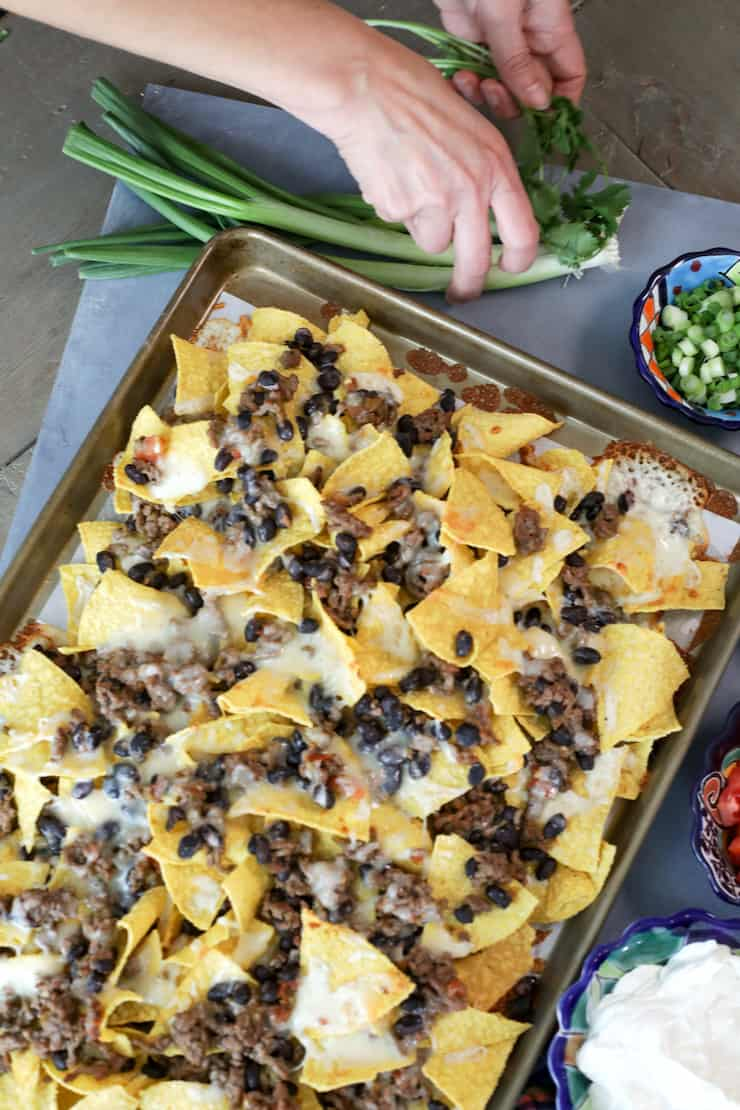 sheet pan of baked classic nachos with hands grabbing cilantro and green onions for garnish