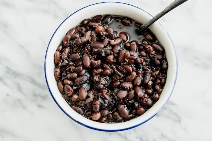 brothy black beans in a white bowl with a blue rim