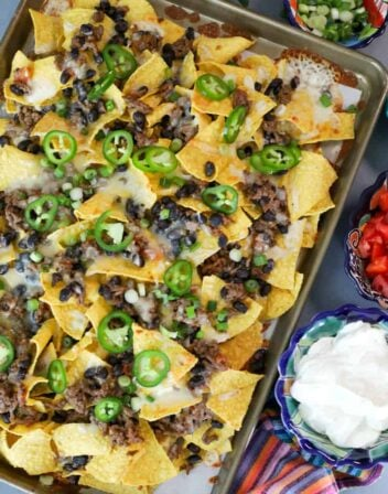 overhead shot of classic sheet pan nachos with several bowls of toppings on the side