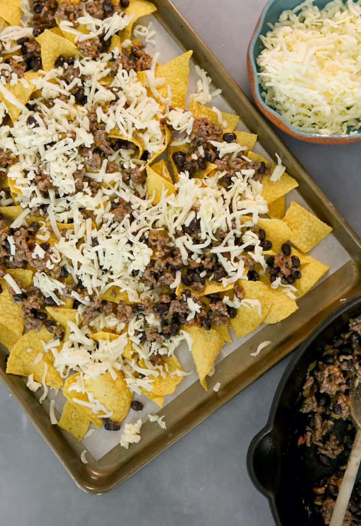 first layer of classic nachos on sheet pan - chips, meat mixture and shredded cheese before baking