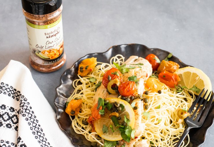 veracruz style white fish over pasta with a bottle of tastefully simple seasoning blend
