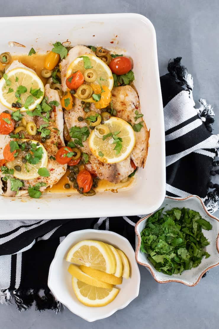 Baked Tilapia Veracruz in a white square baking dish on a black and white striped dish towel