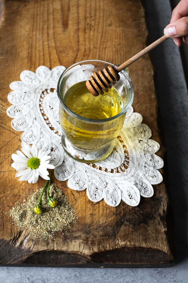 Té de manzanilla (Chamomile Tea) in a clear glass cup with a honey stick. The glass is on a vintage doily on a wood surface