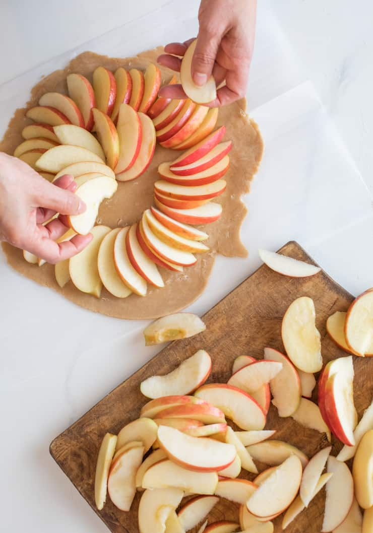 hands arranging apple slices on top of rolled out galette dough