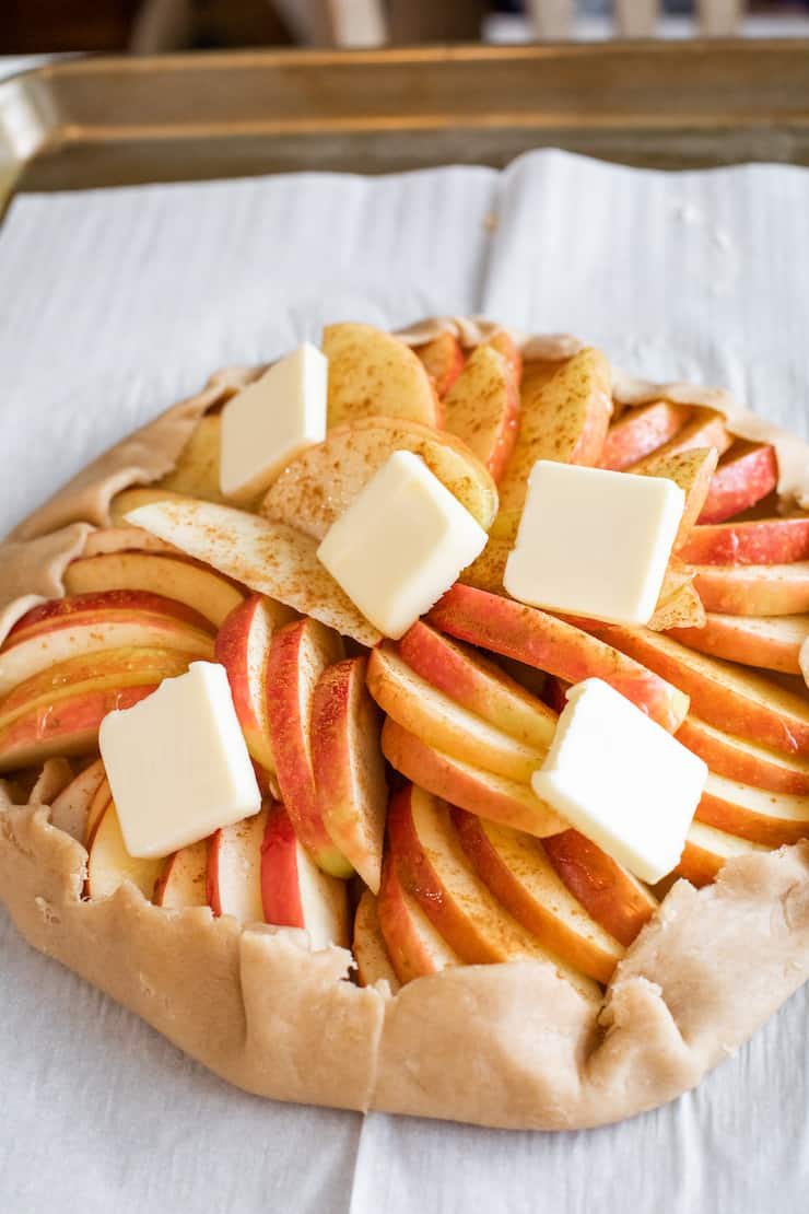 apple galette on a parchment lined sheet tray dotted with butter prior to baking