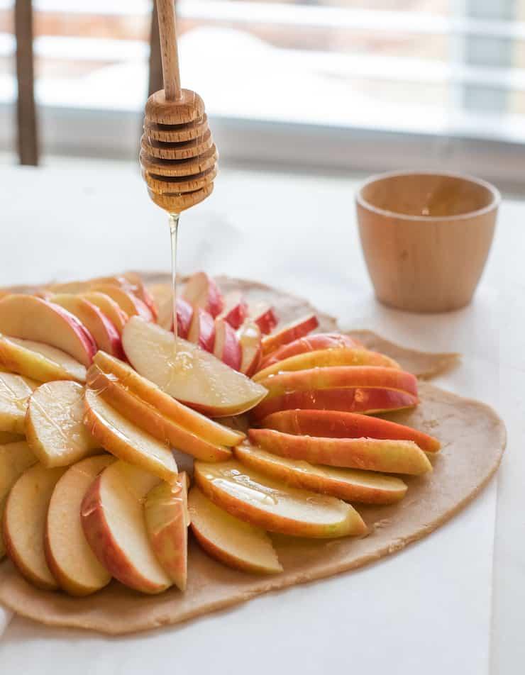 honey dipper drizzling honey onto apple slices for galette