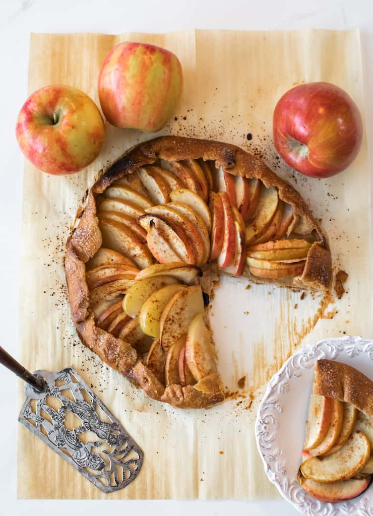 overhead shot of baked apple galette on a cutting board with a slice removed and a silver pie server