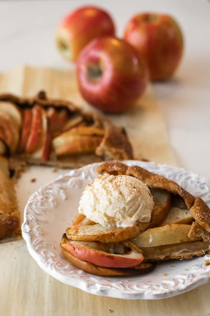 slice of apple galette on a white plate topped with a scoop of vanilla ice cream