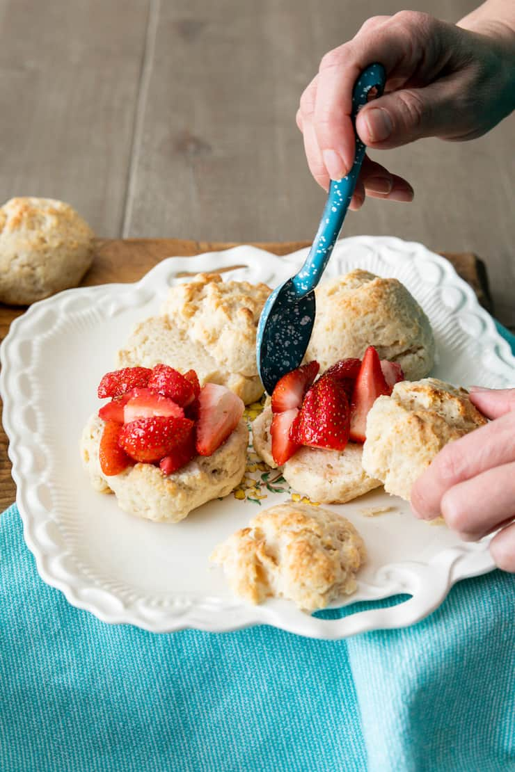 hands assembling homemade strawberry shortcakes out of easy drop biscuits on a white platter