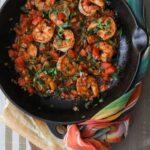 black cast iron sauté pan filled with cooked ranchero style shrimp