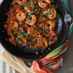 black cast iron sauté pan filled with cooked ranchero style shrimp