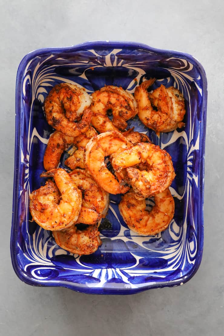 overhead shot of cooked camarones in a blue and white bowl