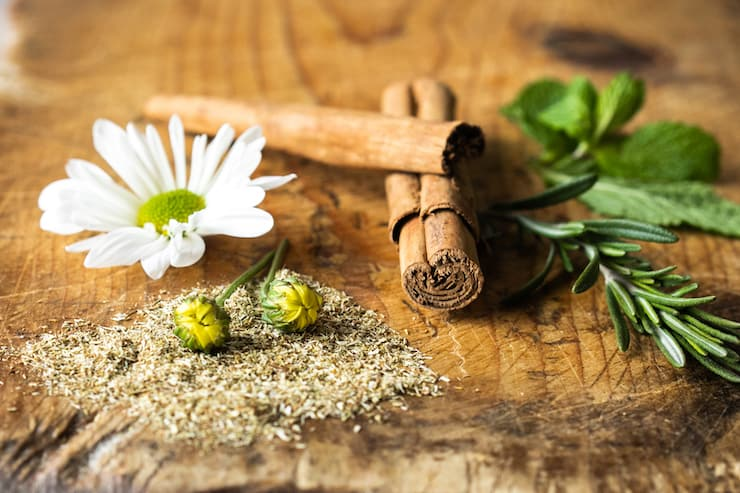 cinnamon sticks, rosemary, chamomile and mint on a wooden board