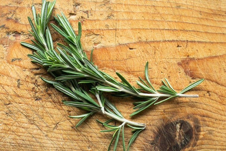 fresh rosemary sprigs on a wooden surface