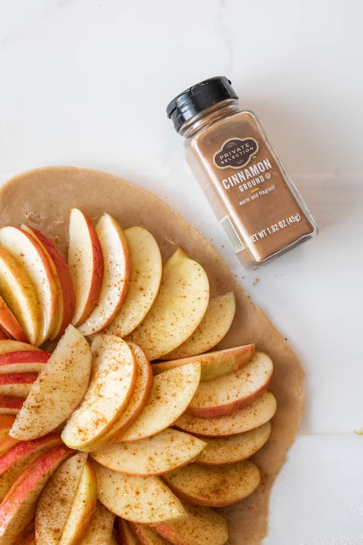 bottle of kroger private collection cinnamon next to unfolded apple galette
