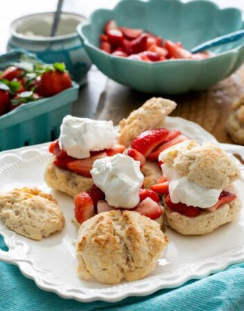 homemade strawberry shortcakes on a white platter with a turquoise linen