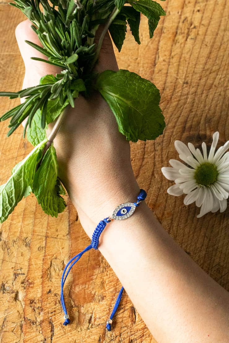 hand holding a bouquet of fresh herbs and wearing an evil eye bracelet