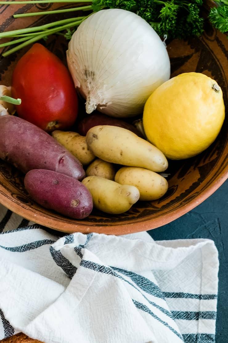 bowl of produce to make Veracruz soup - onion, garlic, tomato, lemon, potatoes