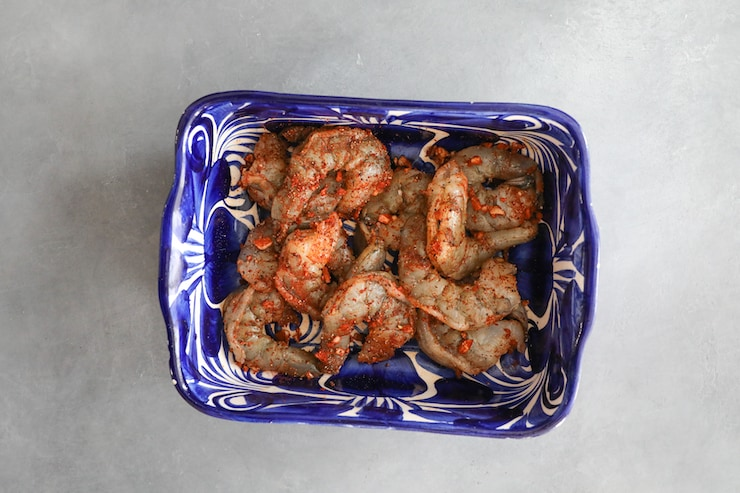 raw shrimp tossed in paprika garlic spice mix in blue and white bowl