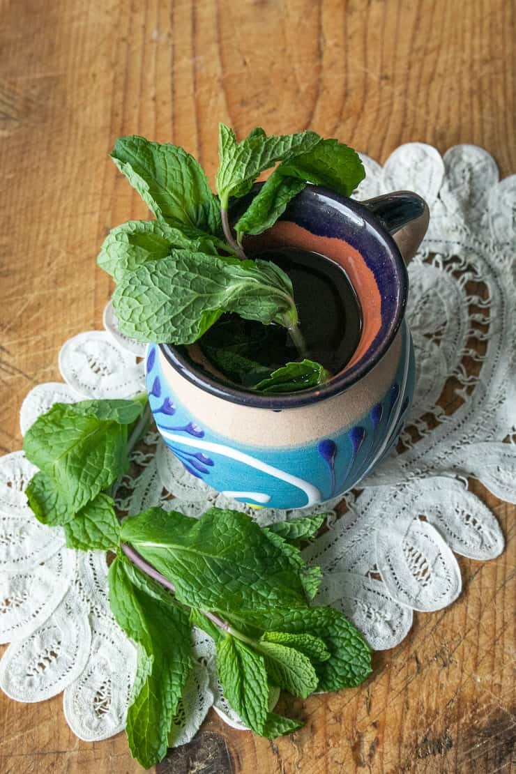 Hierbabuena (Mint Tea) in a Mexican pottery cup on a vintage white doily and wood background