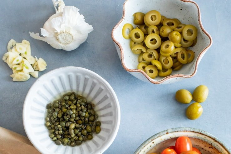 bowls of capers, olives and tomatoes on a grey surface