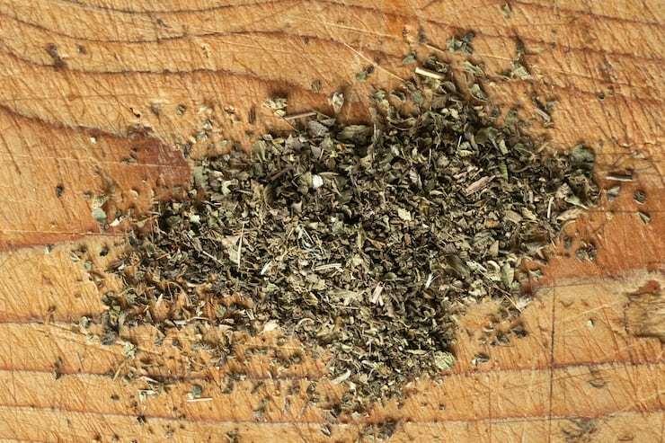dried Oregano sprinkled on a wooden surface