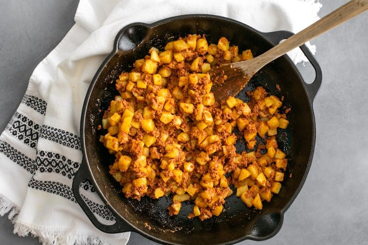 overhead shot of black cast iron skillet filled with papas con chorizo, a wooden spoon and a white and black embroidered linen