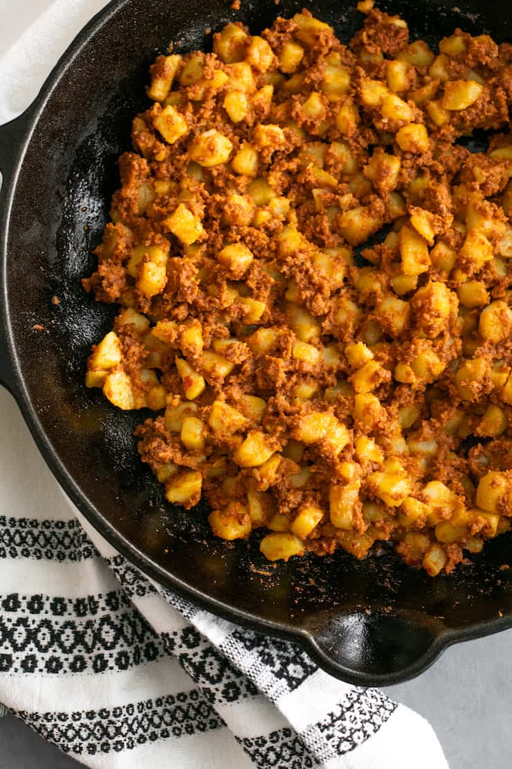 overhead shot of papas con chorizo in a black skillet on a table with a black and white linen