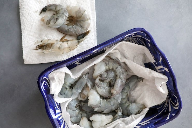 raw shrimp in a blue bowl with paper towels to dry