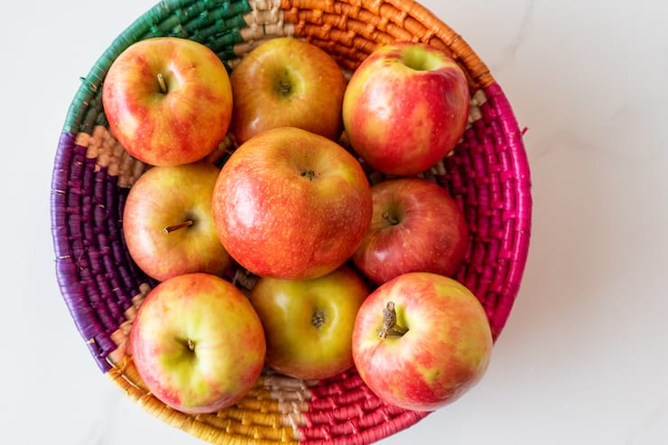 colorful woven basket filled with apples