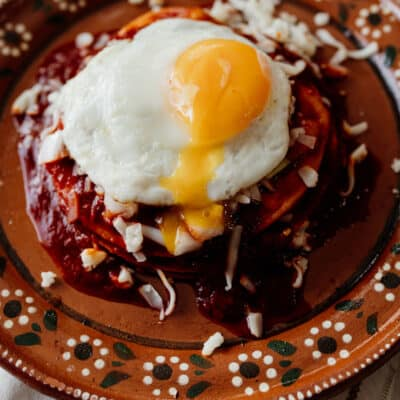 stacked red enchiladas on an earthenware plate with a fried egg on top