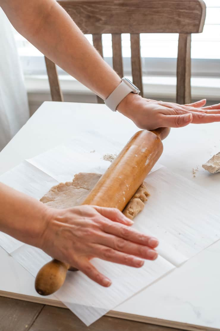 hands using a rolling pin to roll out galette dough on a piece of parchment