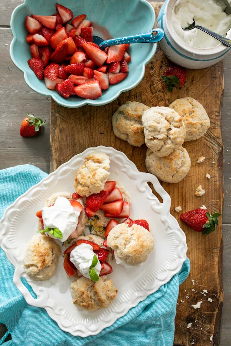 overhead shot of strawberry shortcakes on a white serving platter with a few drop biscuits and a bowl of macerated berries to the side