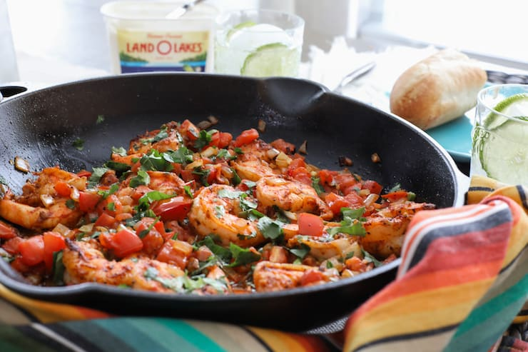 black skillet with ranchero style shrimp and a multicolored linen wrapped around the handle