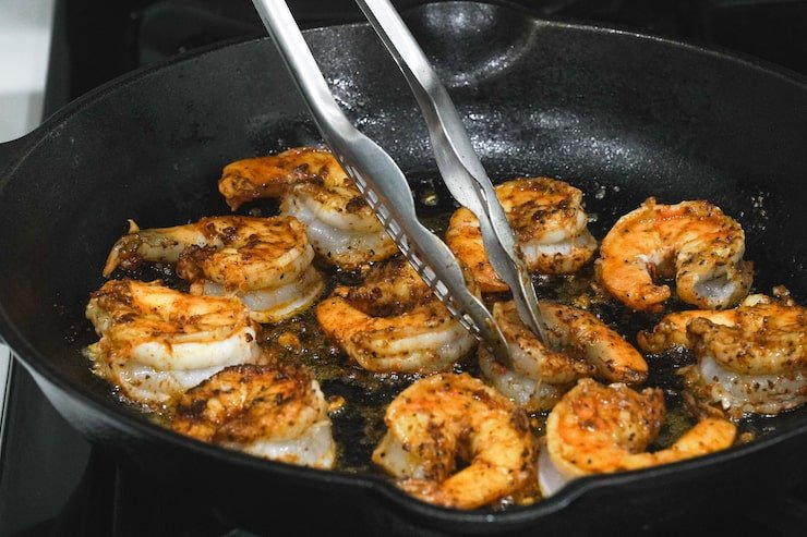 camarones a la mexicana cooking in a black cast iron skillet with silver tongs