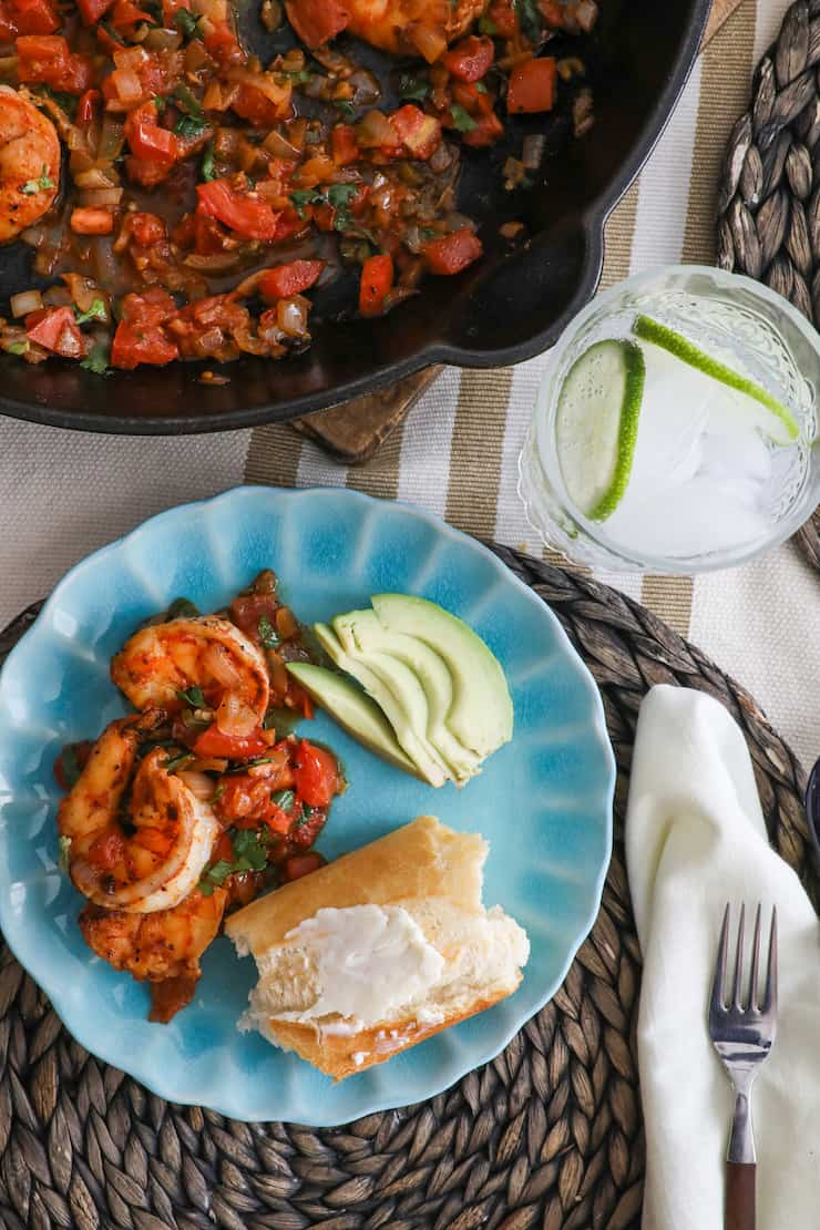 turquoise plate with camarones a la mexicana, sliced avocado and crusty bread topped with butter next to a pan full of mexican ranchero style shrimp