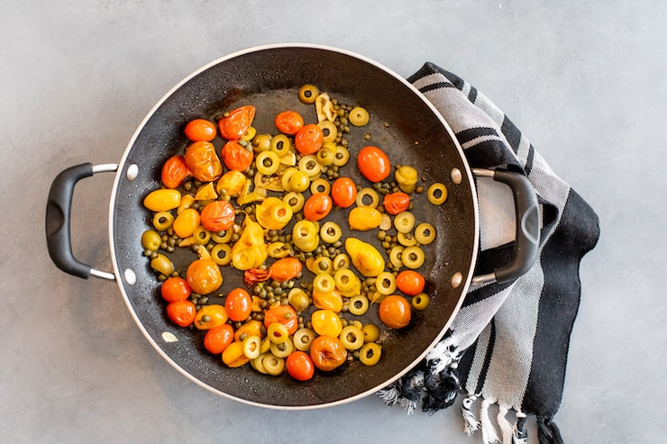 tomatoes, olives and capers in a skillet