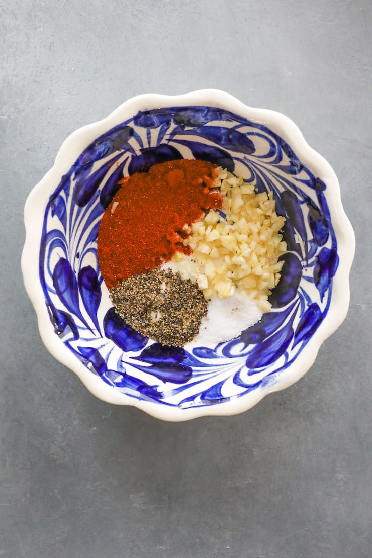 blue and white patterned bowl with salt, pepper, garlic and paprika to coat shrimp