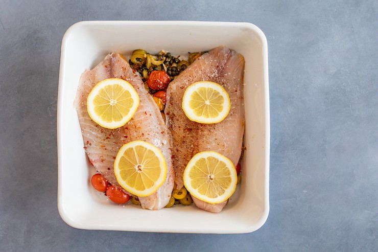square baking dish with fish fillets atop caper/olive tomato mixture and topped with lemon slices