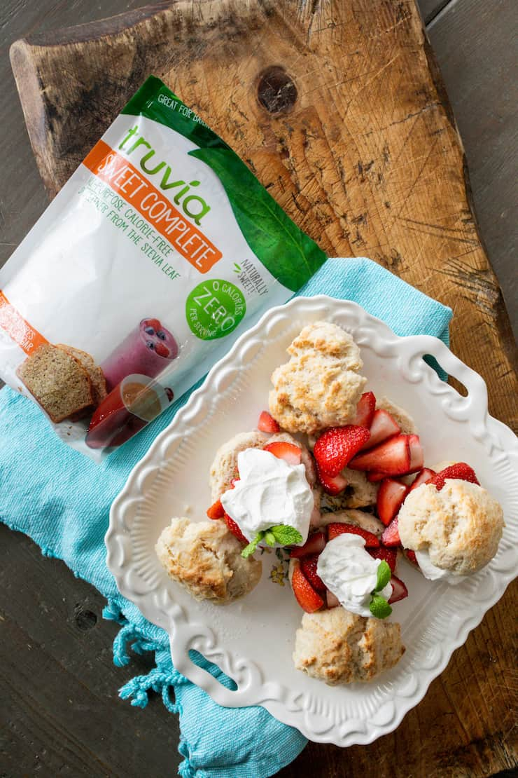 overhead shot of a bag of truvia sweet complete next to a white platter with strawberry shortcakes