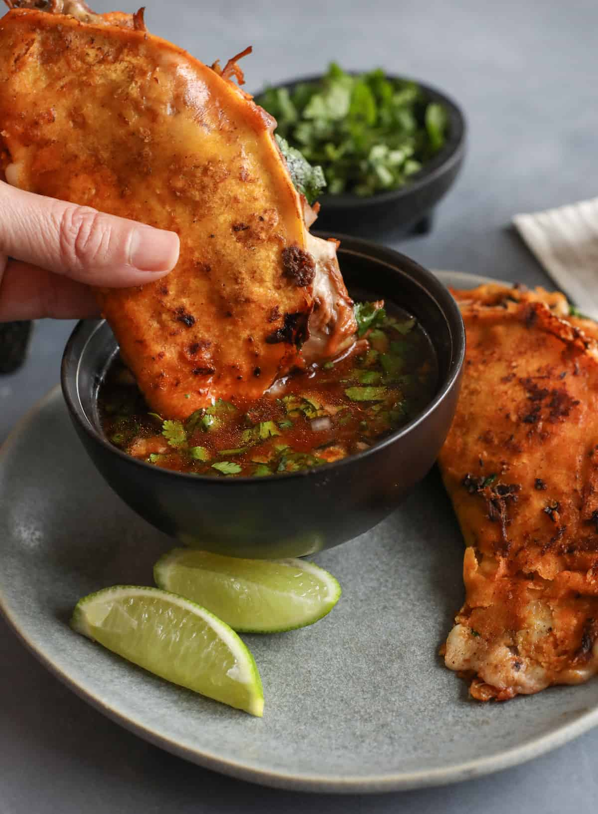 hand dipping cheesy quesabirria taco into birria sauce