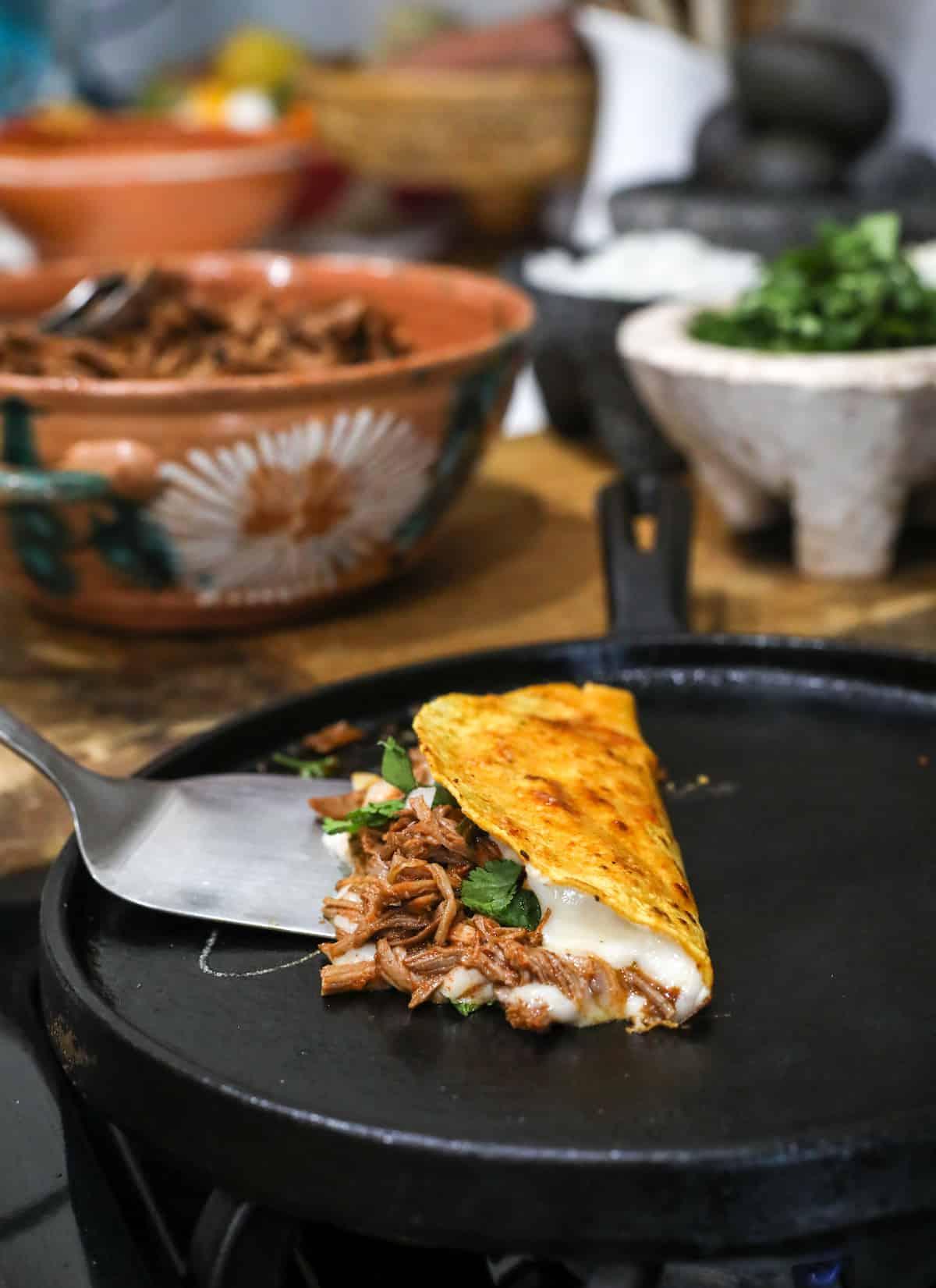 a cheesy birria de res taco on the comal with a silver spatula
