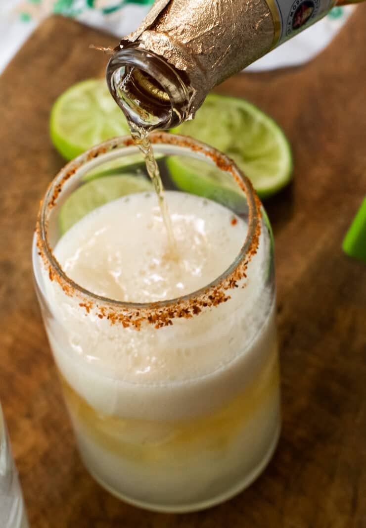 close up shot of Modelo beer being poured into a glass with ice and lime juice that has been rimmed with chili lime salt for a chelada