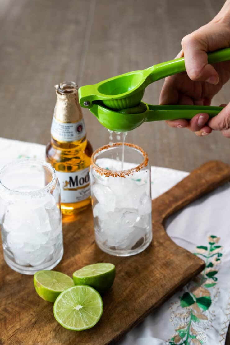 hand squeezing lime juice into a glass of ice that has been rimmed with tajin seasoning