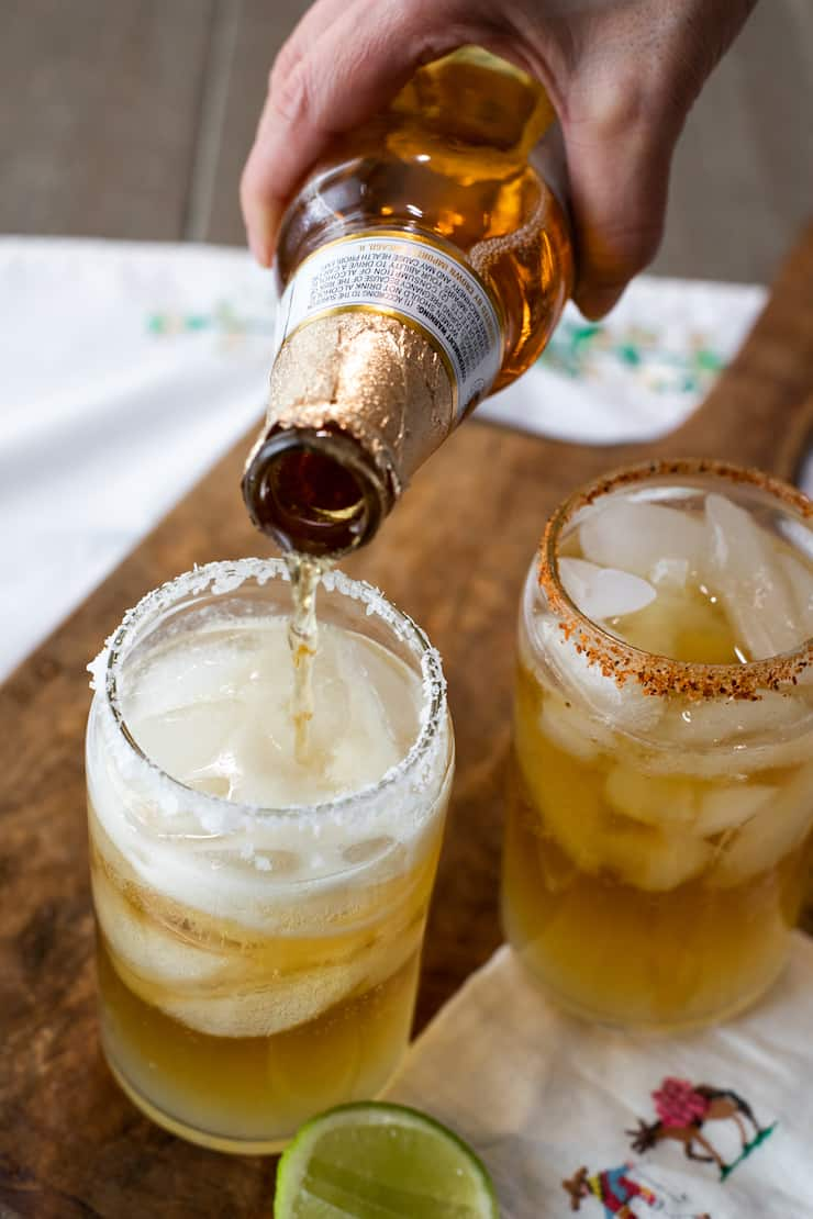 hand pouring modelo beer into salt rimmed glass with ice and lime juice