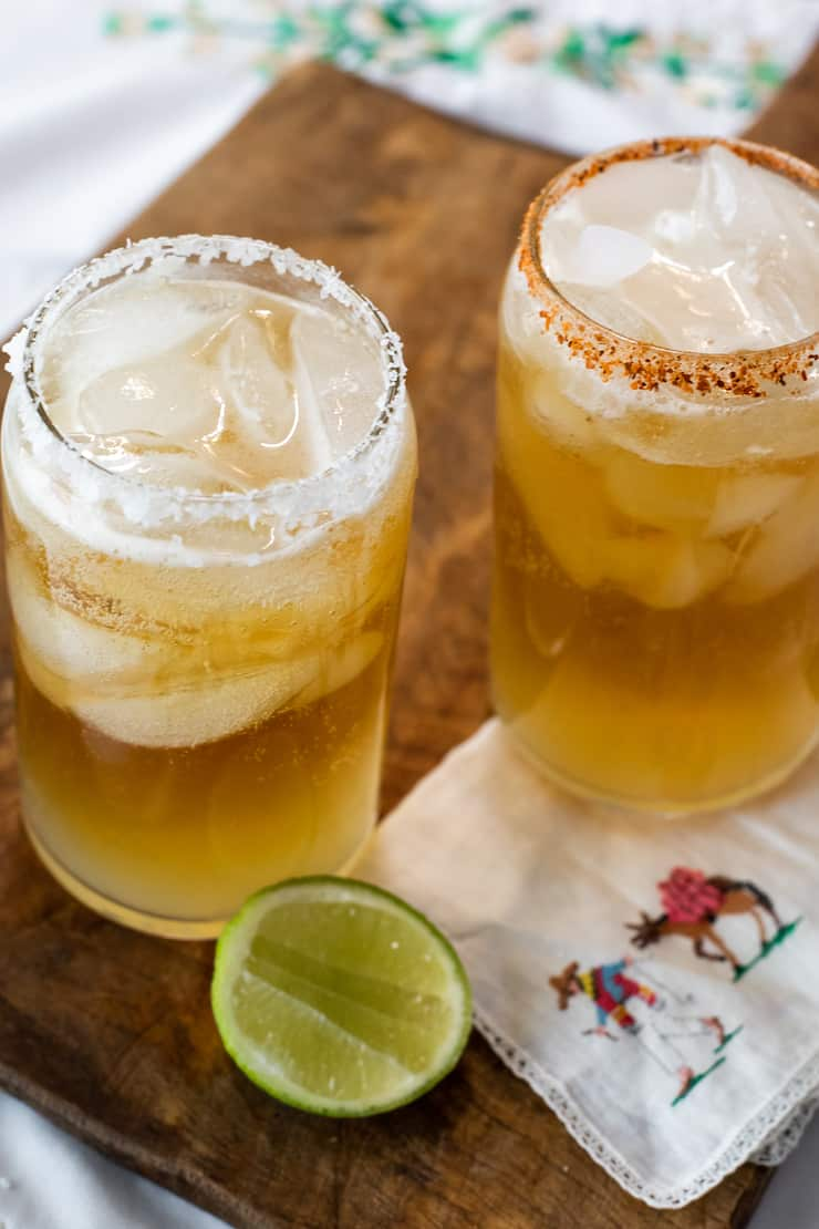 two chelada beer cocktails in clear glasses with salted rims on a wooden cutting board