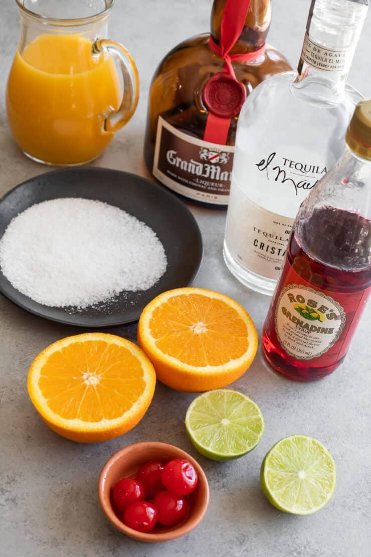 orange juice, grand marnier, tequila, grenadine and fresh fruit laid out for making frozen sunrise margaritas