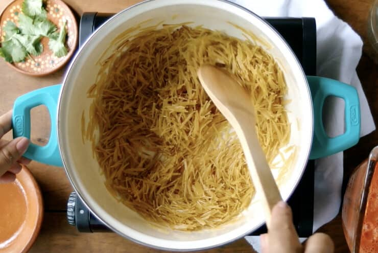 fideo being toasted in a blue pot stirred with a wooden spoon